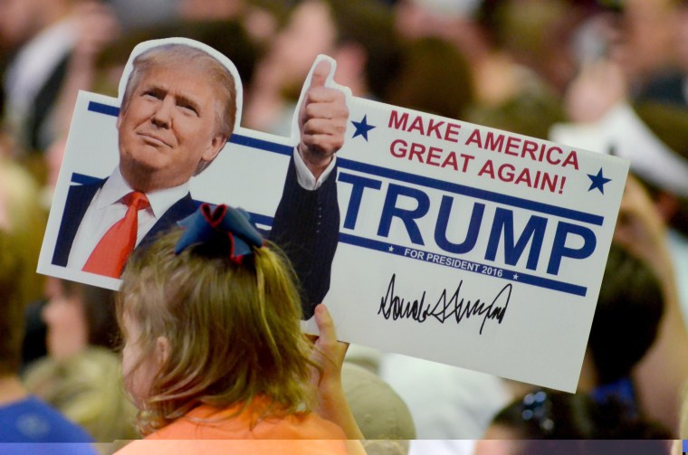 Image: A young supporter holds up a campaign sign for U.S. Republican Presidential candidate Donald Trump at a campaign rally in Madison Mississippi