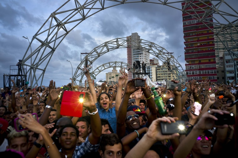 Image: Fans dance and take pictures with their mobile phones during a free concert in Havana