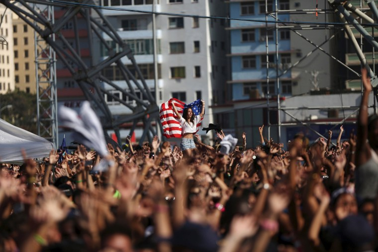 Image: A woman holds a U.S. flag during a performance by U.S. electronic music group Major Lazer in Havana