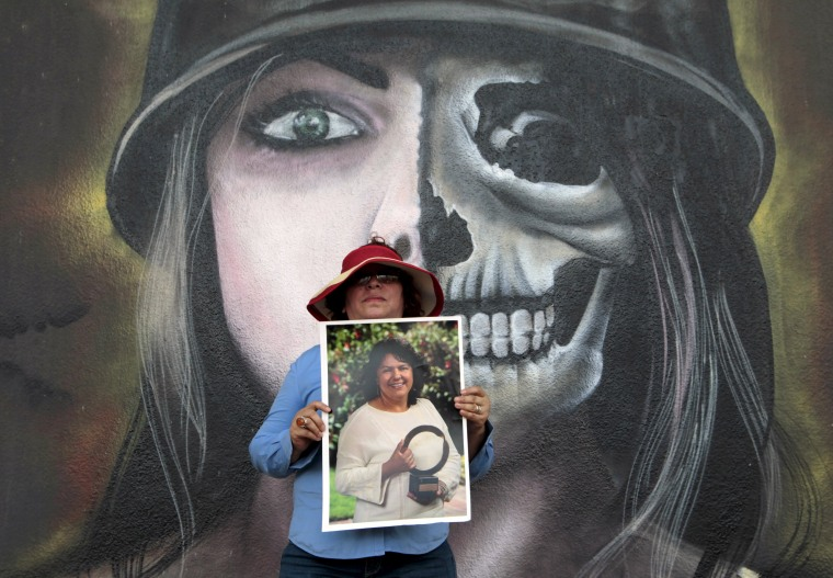 Image: An activist poses with a photos of slain environmental rights activist Berta Caceres during a march in Managua