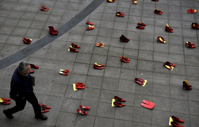 Image: A man walks past a group of red shoes used for a performance to denounce violence against women organized by Amnesty International during International Women's Day in Gijon