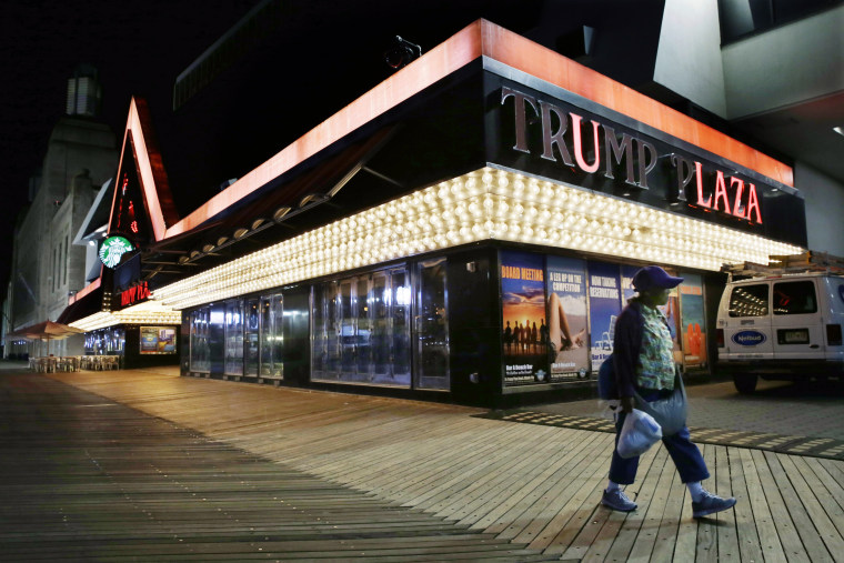 A woman passes burned-out lights at the Trump Plaza Hotel & Casino on The Boardwalk in Atlantic City, N.J., on Sept. 16, 2014.
