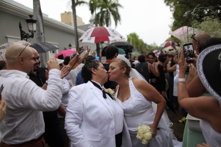 Alma Rosado,left, and Flor Maria Montijo, right, kiss after a mass same-sex wedding in San Juan, Puerto Rico, on Aug. 16, 2015. Over 60 couples from around the region gathered in Puerto Rico's capital to exchange vows at a same-sex marriage ceremony.