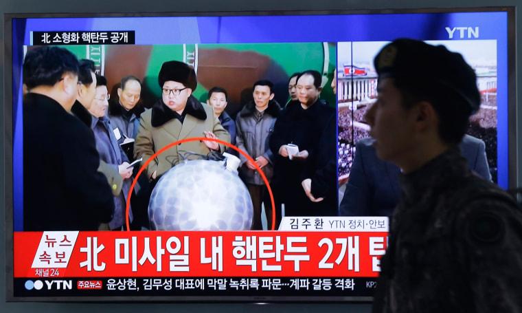 Image: A South Korean army soldier walks by a TV screen showing North Korean leader Kim Jong Un