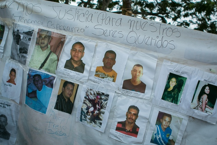 Banner with the photos of the 28 missing Venezuelan miners.