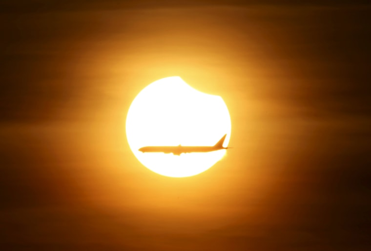 Image: An aeroplane flies past the sun as it goes into a partial solar eclipse in Singapore