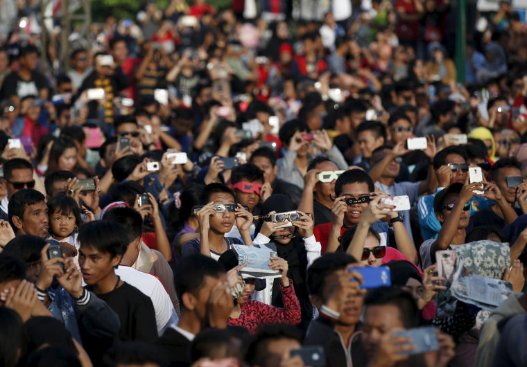 Image: People watch a solar eclipse near the Ampera Bridge along the banks of the Musi River in Palembang, South Sumatra province, Indonesia