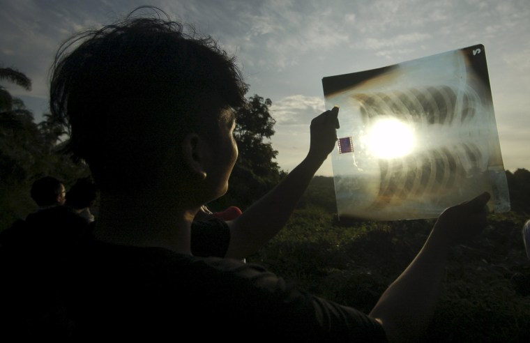 Image: A person uses a medical X-ray film to view the sun during a solar eclipse in Silaut