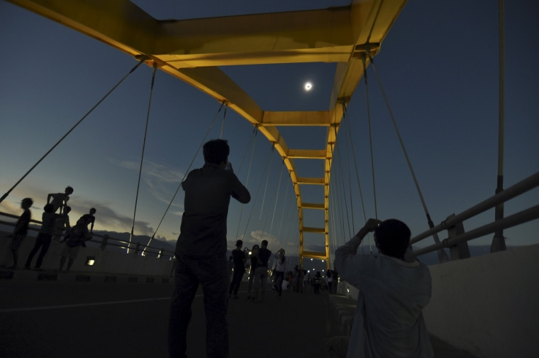 Image: People watch a total solar eclipse from the Bay Bridge in Palu, Central Sulawesi, Indonesia