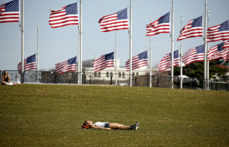 Image: A woman sunbathes on a unseasonably warm day in Washington
