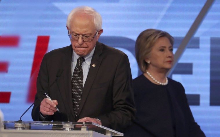 Image: Democratic U.S. presidential candidate Senator Bernie Sanders writes as his rival Hillary Clinton walks behind him during a commercial break at the Univision News and Washington Post Democratic U.S. presidential candidates debate in Kendall