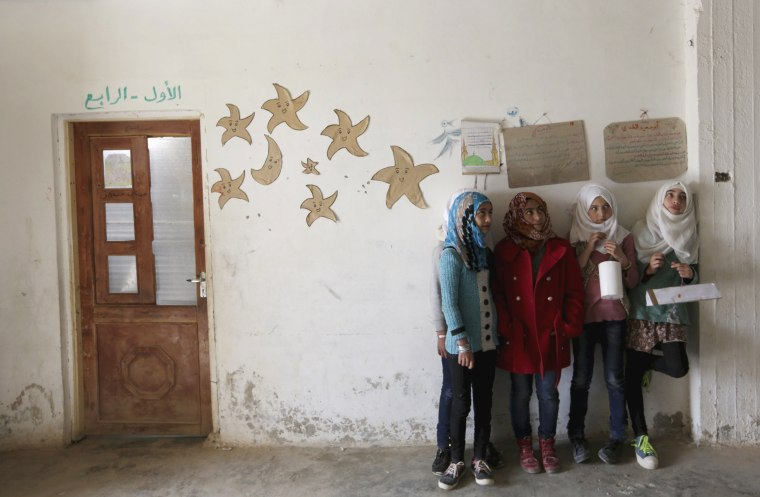 Image: Students hold geometrical forms to decorate the Freedom School, in the town of al-Tamanah, in the southern countryside of Idlib