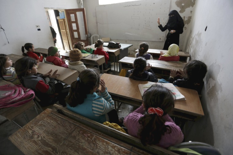 Image: Students attend a class inside the Freedom School, in the town of al-Tamanah, in the southern countryside of Idlib