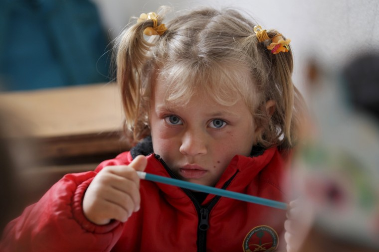 Image: A student attends a class inside the Freedom School, in the town of al-Tamanah, in the southern countryside of Idlib