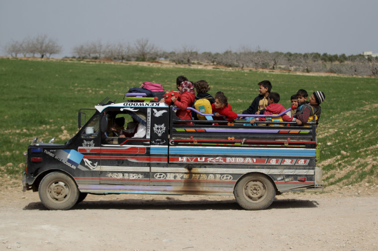 Image: Students ride on a pick-up truck after leaving the Freedom School, in the town of al-Tamanah, in the southern countryside of Idlib
