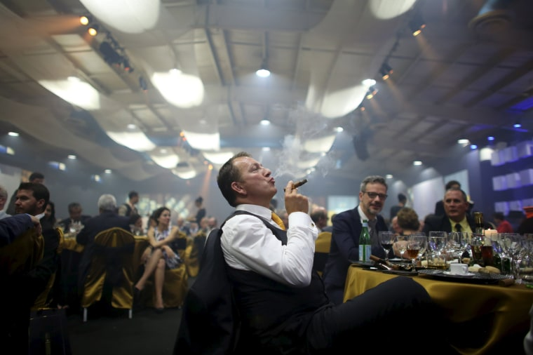 Image: Juan Philippe from France enjoys a cigar during the gala dinner of the closing of the XVIII Habanos Festival in Havana