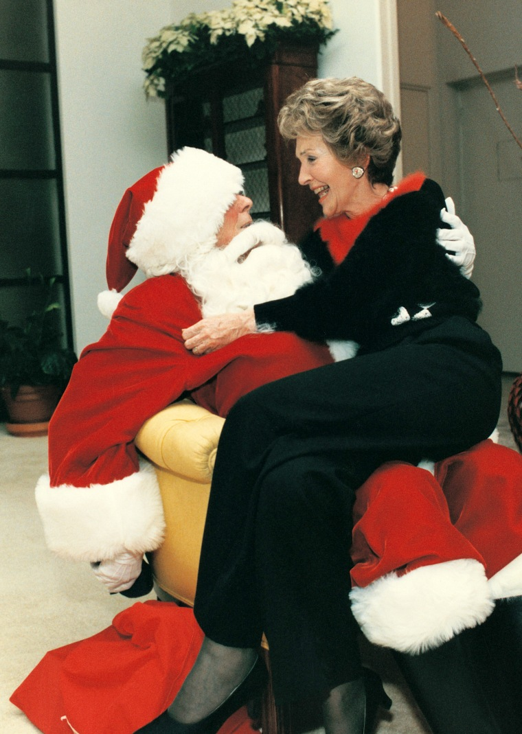 Nancy Reagan talks with Santa also known as her husband, Ronald.