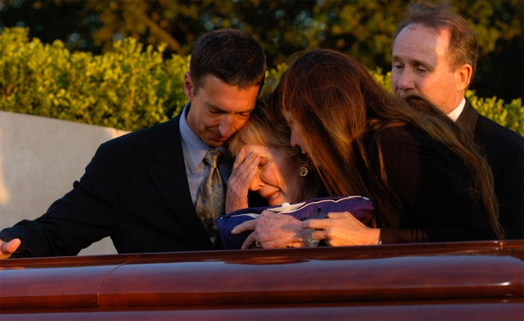 Nancy Reagan is joined by son Ron Reagan, left, son Michael Reagan, back right, and daughter Patti Davis as she cries over the coffin bearing her husband Ronald Reagan during interment ceremonies for the former president at the Ronald Reagan Presidential Library in Simi Valley, Calif., June 11, 2004.