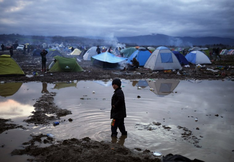Image: A migrant boy stands in a puddle in a makeshift camp on the Greek-Macedonian border, near the village of Idomeni