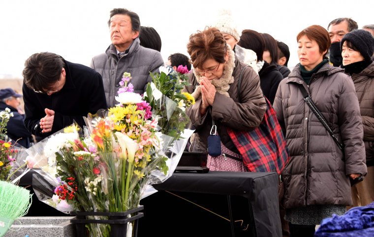 Image: People pray for victims at an alter in Sendai, northern Japan