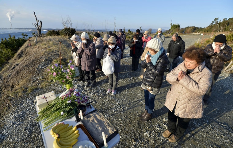Image: People pray toward the sea in remembrance of the victims