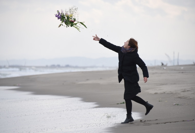 Image: A woman throws flowers into the sea to honor the victims