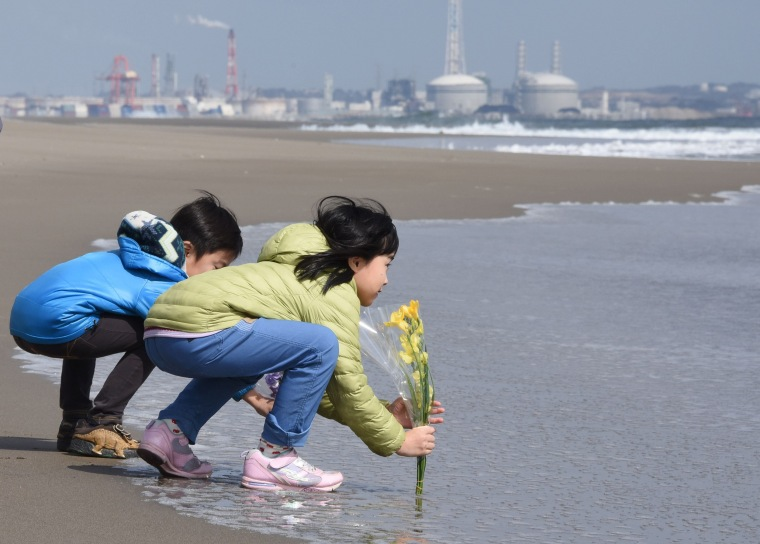Image: A sister and brother lay flowers on the beach in Sendaifor, in memory of the victims