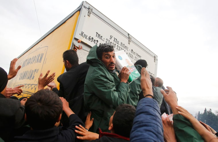 Image: Migrants try to get products from a truck at a makeshift camp on the Greek-Macedonian border near the village of Idomeni