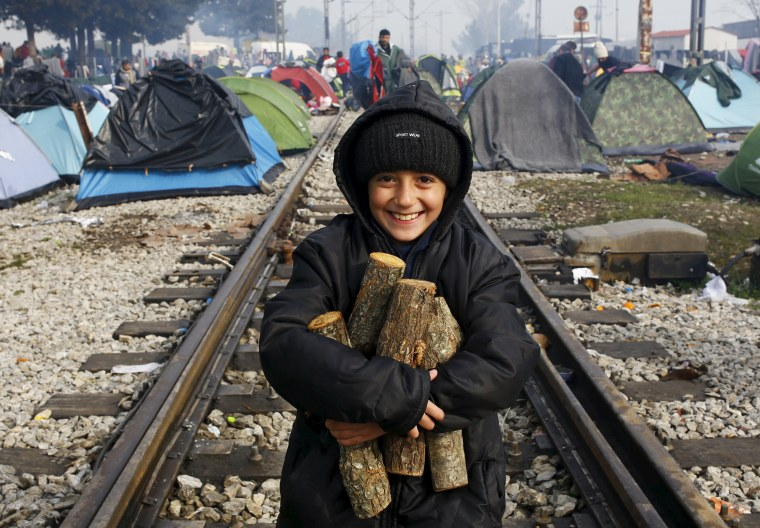 Image: A migrant child, waiting to cross the Greek-Macedonian border, carries firewood along a railway track during a foggy early morning near the village of Idomeni