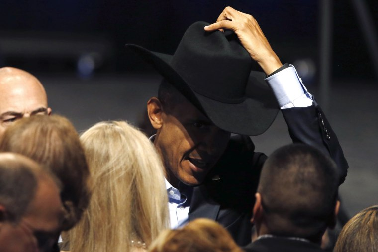 Image: Obama tries on a supporter's cowboy hat after delivering remarks at a DNC event at Gilley's Club in Dallas, Texas