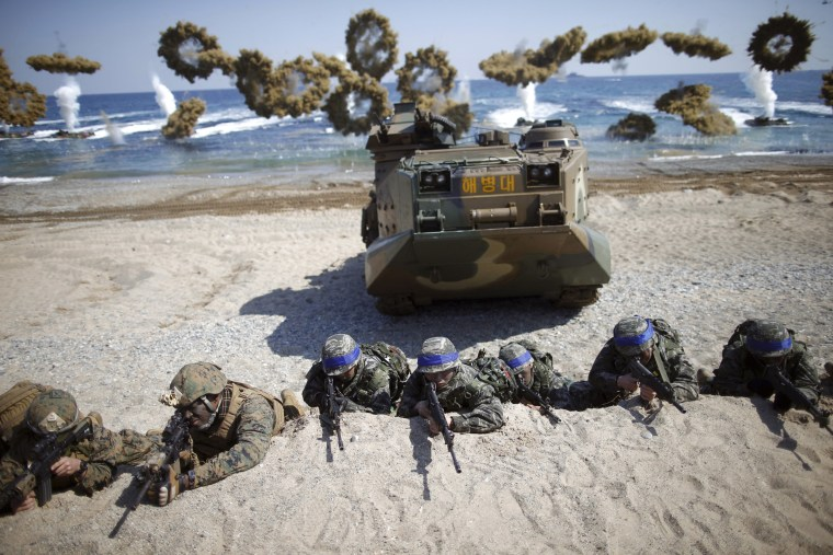 Image: South Korean and U.S. Marines take positions as amphibious assault vehicles of the South Korean Marine Corps fire smoke bombs during a U.S.-South Korea joint landing operation drill in Pohang