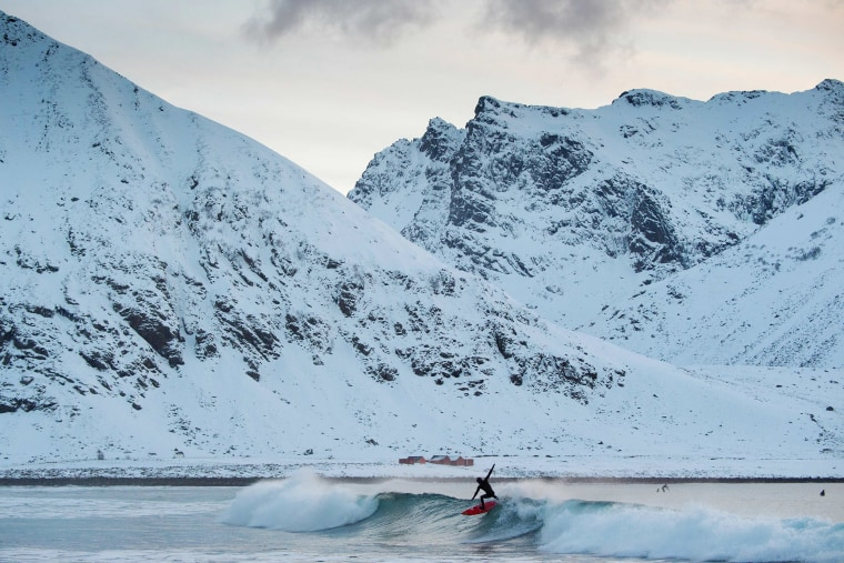 Image: Snow covered mountains backdrop a surfer in Unstad
