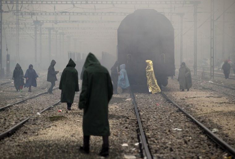 Image: Migrants walk on railway tracks at the northern Greek border station of Idomeni