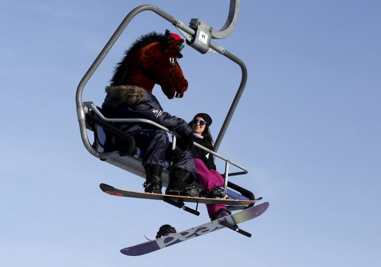 Image: A snowboarder wearing a mask of a horse head rides a lift uphill at the Bobrovy Log ski resort in the suburbs of Krasnoyarsk