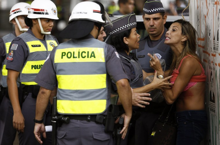 Image: A demonstrator argues with policewomen after she turned up her shirt