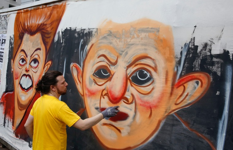 Image: A street artist spray paints caricatures of Brazil's former President Luiz Inacio Lula da Silva, center, and current President Dilma Rousseff