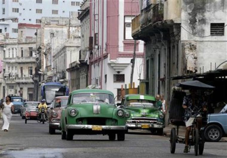 Cars drive on a street in Havana