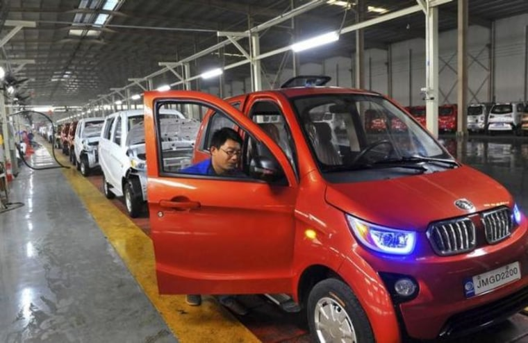 An employee assembles an electric car along a production line at a factory in Qingzhou