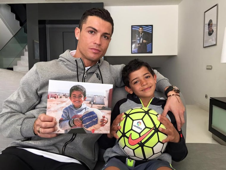 """Cristiano Rolando poses with a Syrian child called """"Ayman"""" for Save The Children."""