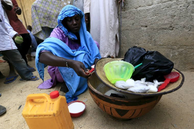 Image: A woman sells milk at a community of internally displaced people