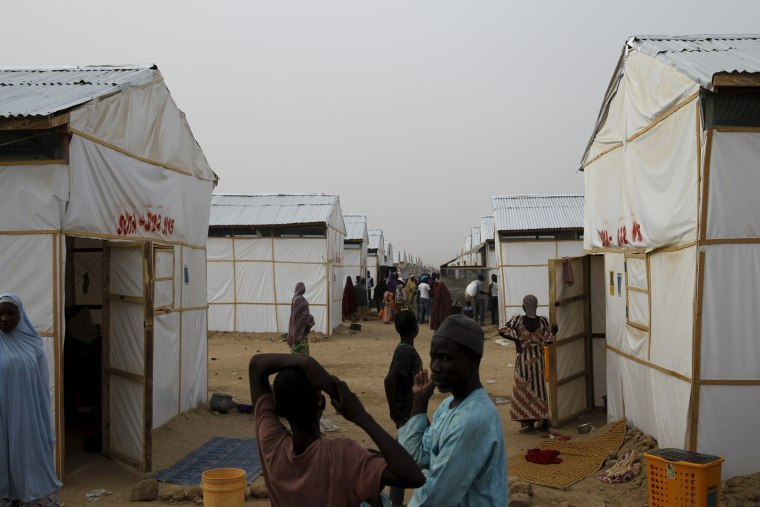 Image: People walk near makeshift accommodation at Bakassi Camp for internally displace people