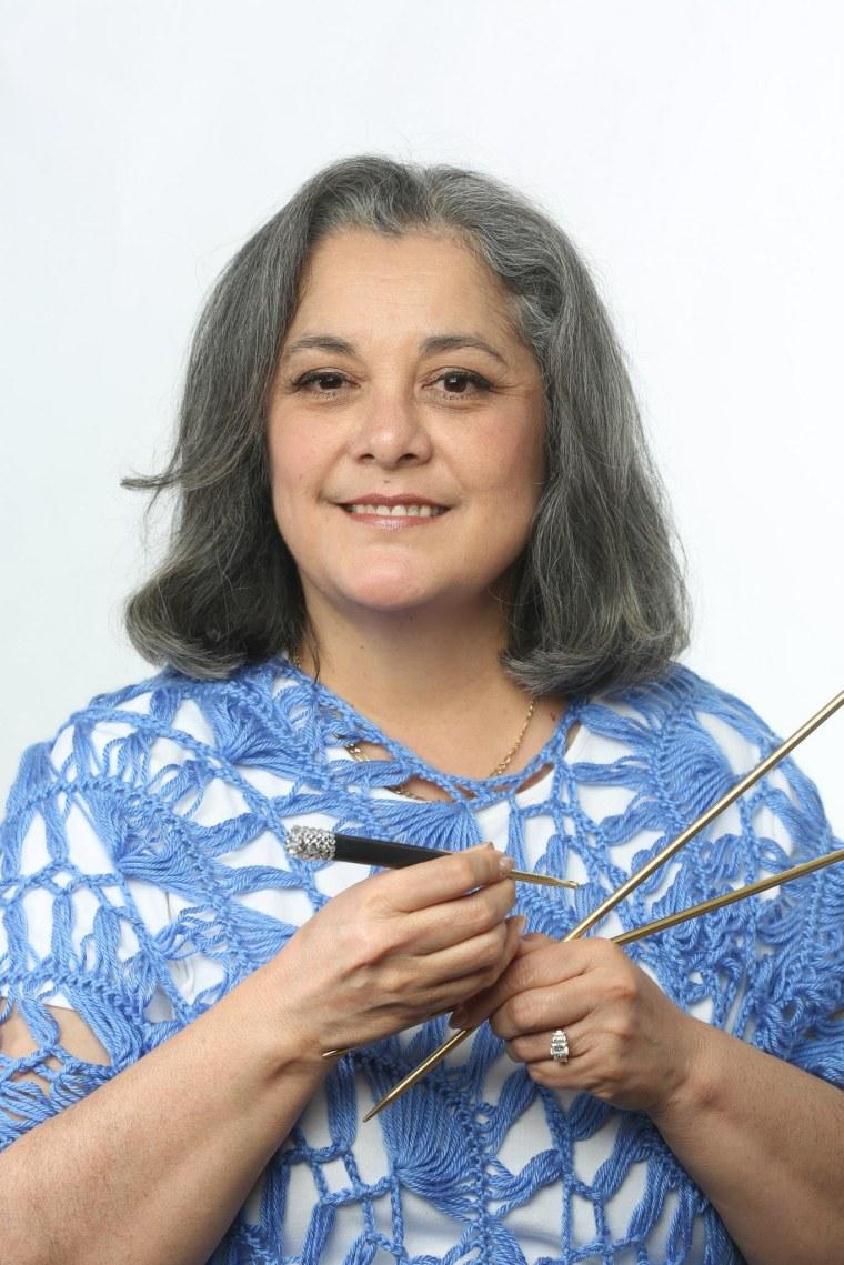 Yolanda Soto-Lopez holding knitting needles and a hook.