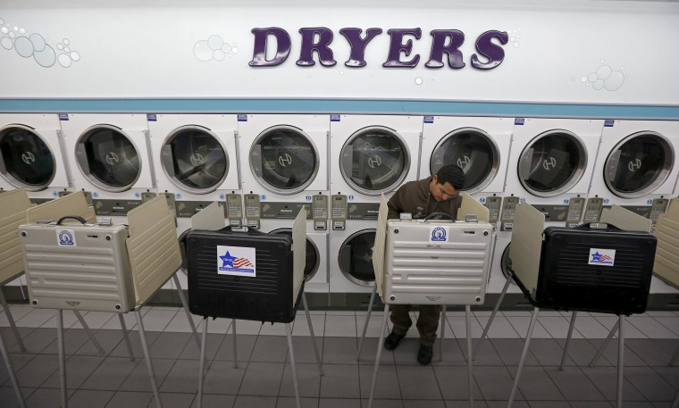 Image: A voter casts a ballot at Su Nueva laundromat during voting in Illinois' U.S. presidential primary election in Chicago
