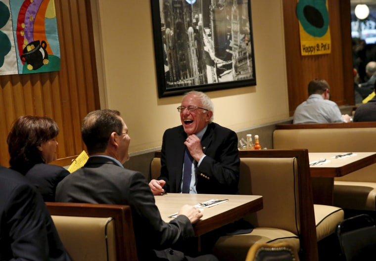 Image: Democratic U.S. presidential candidate Bernie Sanders laughs after sitting down for breakfast at Lou Mitchell's Restaurant in Chicago, Illinois