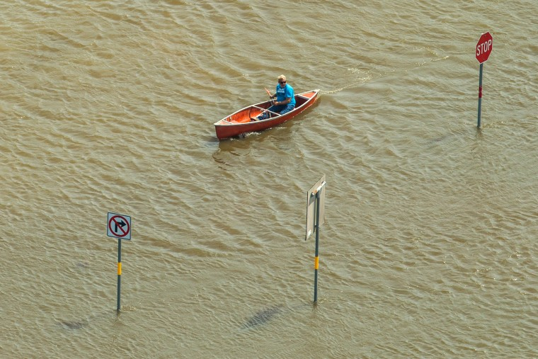 Image: A  man travels by canoe in floodwater
