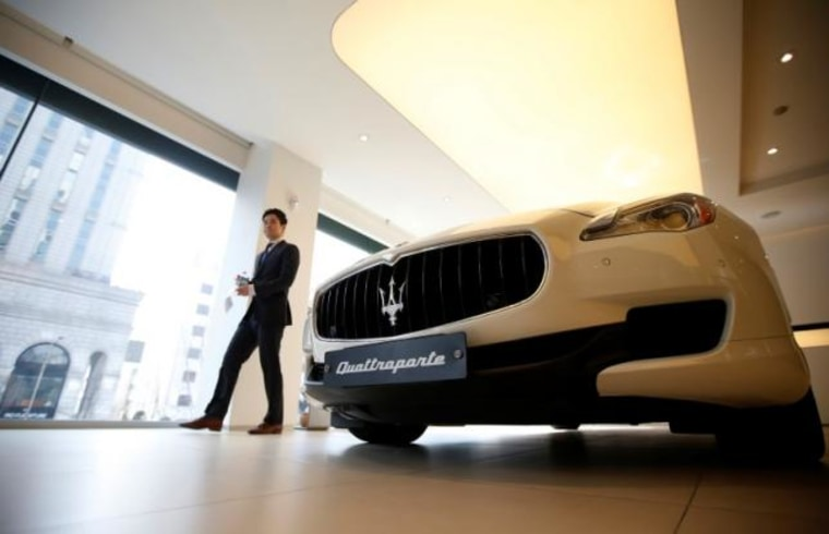 A car dealer walks past a Maserati Quattroporte car at a its dealership in Seoul