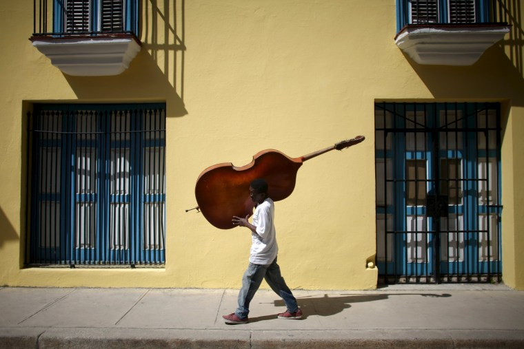 Image: Musician Frilal Ortiz carries a double bass in downtown Havana