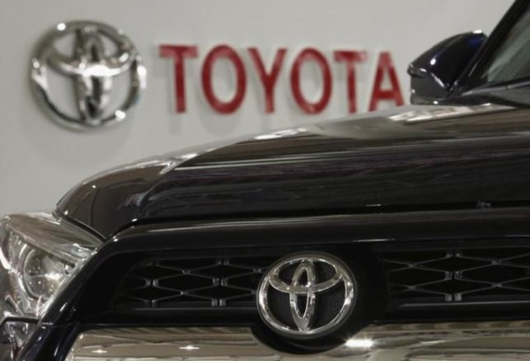 A logo of Toyota Motor Corp is pictured on a car and the background at the company's showroom in Tokyo