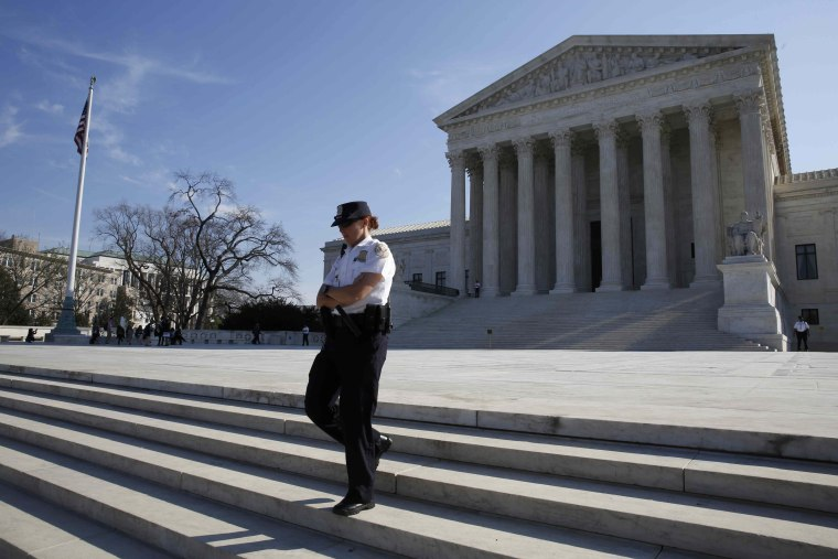 Image: A U.S. Supreme Court police officer descends the steps outside the court in Washington