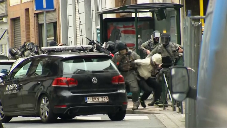 Armed security officers dragged a man from a Molenbeek apartment at gunpoint after shots were fired in a terror raid related to the November Paris attacks.